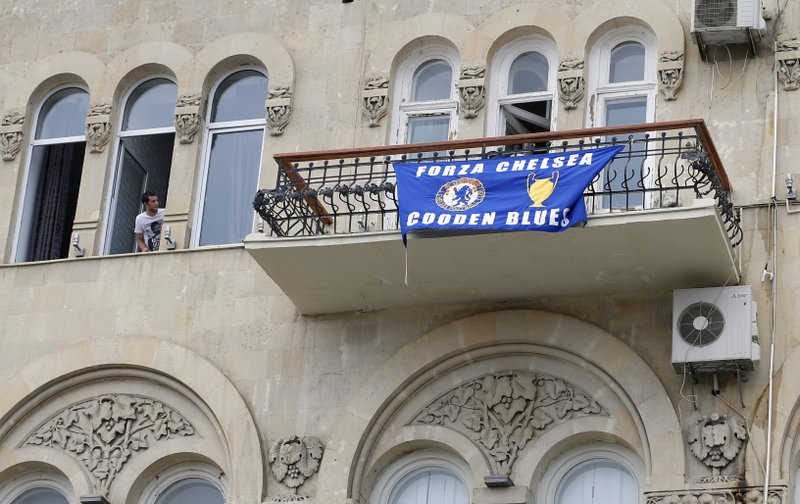 A man looks from a window at the Chelsea soccer team flag on a balcony in central Baku, Azerbaijan Tuesday, May 28, 2019. Supporters were arriving in the Azerbaijan capital ahead of Wednesday's Europa League final between English teams Arsenal and Chelsea. (AP Photo/Darko Bandic)