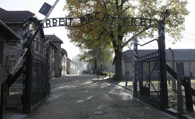 This Friday, Oct. 19, 2012 photo shows the entrance to the former Nazi German Auschwitz death camp with the inscription 'Arbeit Macht Frei' (Work Sets You Free) in Oswiecim, Poland. A Polish court has sentenced two Belarusian men to prison for organizing a 2017 stunt in which young adults stripped naked at Auschwitz and chained themselves together to the 'Arbeit Macht Frei' gate as one man slaughtered a sheep.(AP Photo/Czarek Sokolowski, file)