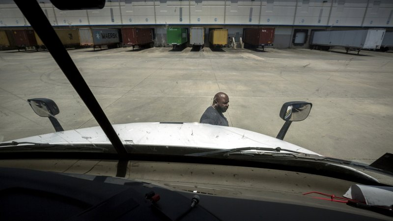 In this Wednesday, May 22, 2019 photo, Leon Brown walks around his truck to secure his trailer during a pick up outside the Port of Savannah, in Garden City, Ga. Brown is trusted enough to drive the tractor-trailer inside one of the nation's busiest seaports more than six years after being released from prison. But is cut off from voting due to a vaguely worded law that state election officials interpret in the strictest possible manner. (AP Photo/Stephen B. Morton)