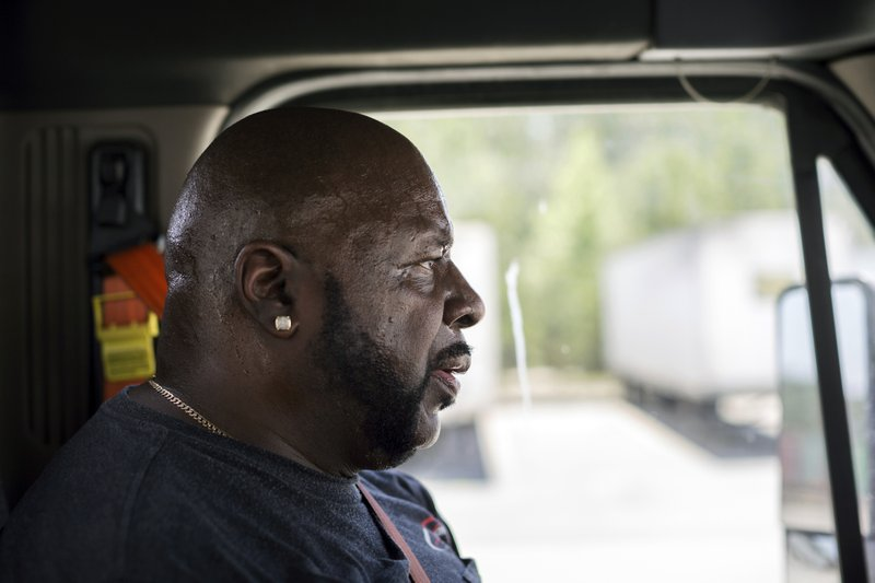 In this Wednesday, May 22, 2019 photo, Leon Brown drives his tractor-trailer on a delivery from a distribution center to the Port of Savannah, in Garden City, Ga. Brown is trusted enough to drive the tractor-trailer inside one of the nation's busiest seaports more than six years after being released from prison. But is cut off from voting due to a vaguely worded law that state election officials interpret in the strictest possible manner.