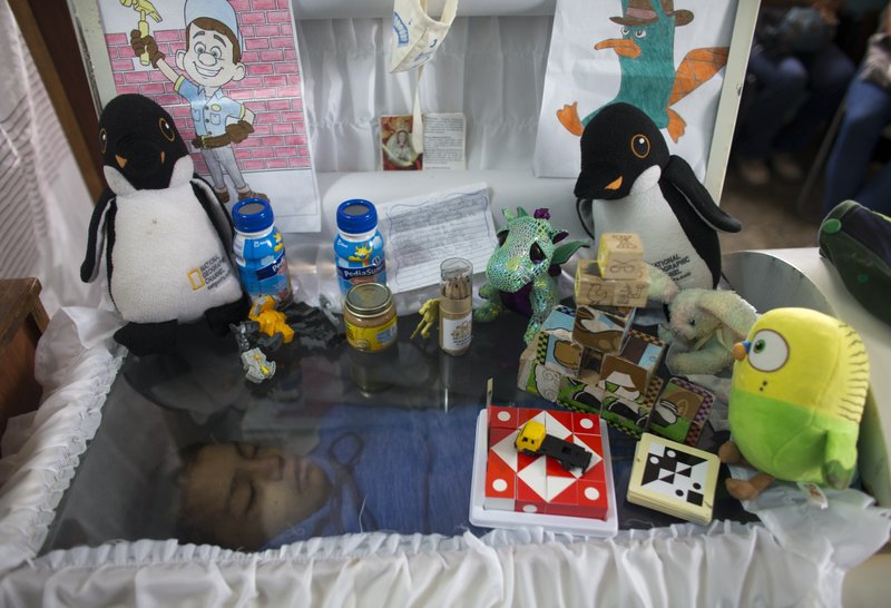Puzzles, stuffed animals and drawings adorn the open casket that contains the remains of 11-year-old Erick Altuve, in his home in the Petare neighborhood in Caracas, Venezuela, Tuesday, May 28, 2019. Erick died while he was waiting for a bone marrow transplant. The deaths of several Venezuelan children with cancer who were hoping for bone marrow transplants have ignited a bitter dispute between the government and opponents over who is to blame. (AP Photo/Ariana Cubillos)