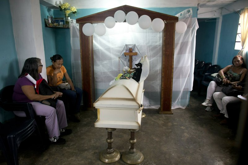 Friends and family attend the funeral of 11-year-old Erick Altuve, in his home in the Petare neighborhood in Caracas, Venezuela, Tuesday, May 28, 2019. Erick died while he was waiting for a bone marrow transplant. The deaths of several Venezuelan children with cancer who were hoping for bone marrow transplants have ignited a bitter dispute between the government and opponents over who is to blame. (AP Photo/Ariana Cubillos)