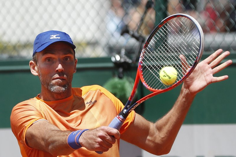 Croatia's Ivo Karlovic plays a shot against Spain's Feliciano Lopez during their first round match of the French Open tennis tournament at the Roland Garros stadium in Paris, Tuesday, May 28, 2019. When 40-year-old Karlovic and 37-year-old Lopez played each other at the French Open on Tuesday, it marked a record for combined age between opponents at Roland Garros in the Open Era. (AP Photo/Pavel Golovkin)
