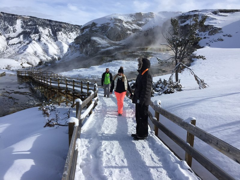 File - In this Jan. 20, 2017, file photo, James Kristy and Ginger Lee of Palm Beach County, Fla., walk the boardwalk at Yellowstone National Park's Mammoth Hot Springs. A federal report shows visitors to Yellowstone National Park spent nearly $513 million in neighboring communities last year. The report last week from the National Park Service indicates the spending by the park's 4.1 million visitors supported nearly 7,100 jobs in the area in 2018. (AP Photo/Matthew Brown, File)