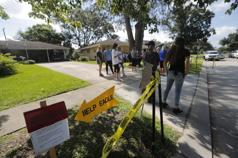 A donation sign is seen as residents and well wishers congregate near a bald eagle nest, waiting for the release of one of its injured eaglets, in Metairie, La., Tuesday, May 28, 2019. A bald eagle hatched this spring in a New Orleans suburb was released Tuesday in the same neighborhood after two weeks in Louisiana State University's Wildlife Hospital. Dozens of neighbors who have watched over the eagle family cheered as the mottled brown bird hopped out of the cage in which it had traveled from Baton Rouge and launched itself into the air. It sat for several minutes on the roof of a house in the shadow of its nest while a pair of mockingbirds dive-bombed it. Then it flew off. The eaglet had been taken to the LSU veterinary school Wildlife Hospital on May 11. It had been found walking in a nearby street, and barely able to fly. (AP Photo/Gerald Herbert)