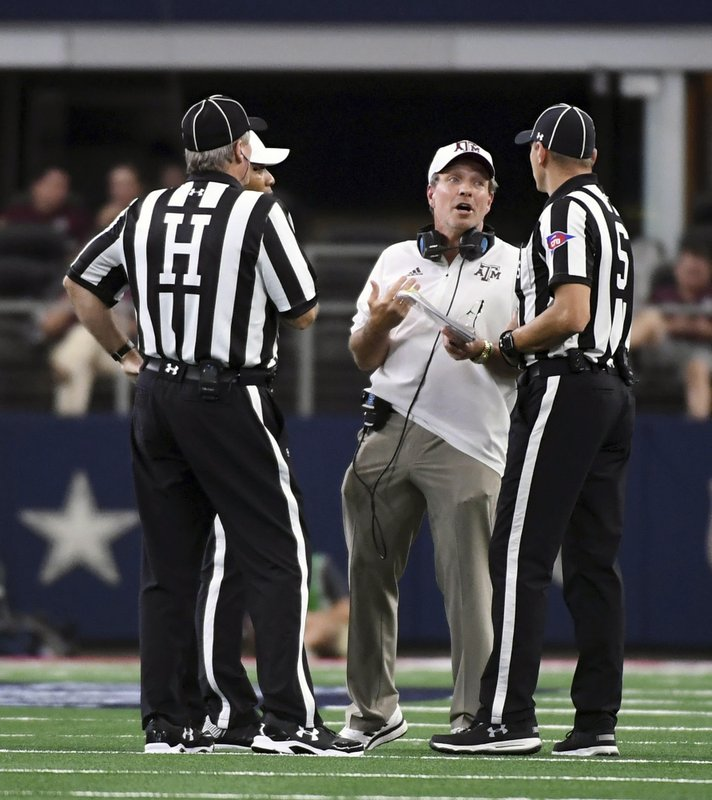 FILE - In this Sept. 29, 2018, file photo, Texas A&M head coach Jimbo Fisher talks to officials during the third quarter of an NCAA college football game against Arkansas, in Arlington, Texas. The Southeastern Conference hired international accounting firm Deloitte to conduct a review of its football officiating. Commissioner Greg Sankey says the move was a reaction in part to the often opinionated view of referees by the public and media.  (AP Photo/Jeffrey McWhorter, File)