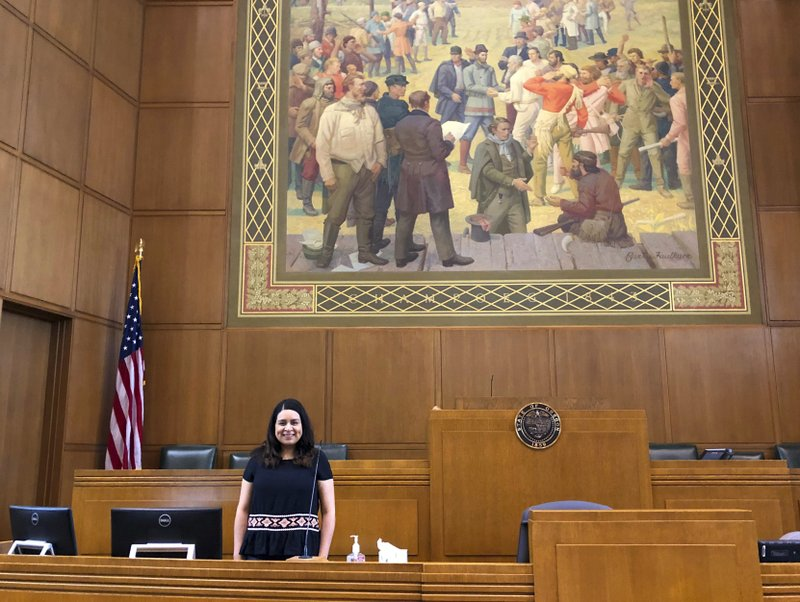 CORRECTS DATE Lacy Ramirez Gruss, the reading clerk in the Oregon House of Representatives, poses for a photo during an interview on the House floor at the Capitol in Salem, Ore., on Friday, May 24, 2019. Republicans, who are in the minority in the House, have insisted since April 30 that bills be read in their entirety, not just by their summaries as is customary, in order to slow down business and try to wrest concessions from Democrats. (AP Photo/Andrew Selsky)