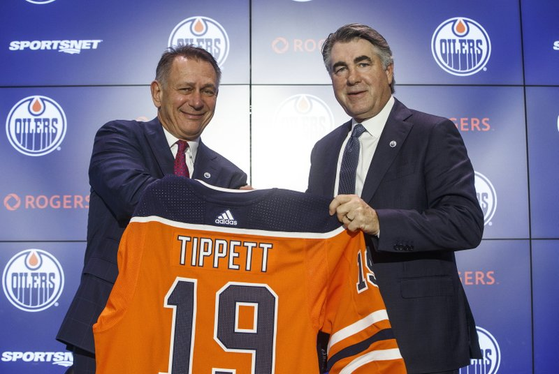 Edmonton Oilers NHL hockey team President of Hockey Operations and General Manager, Ken Holland, left, and new head coach Dave Tippett hold up a jersey during a press conference in Edmonton, Alberta, Tuesday, May 28, 2019. (Jason Franson/The Canadian Press via AP)
