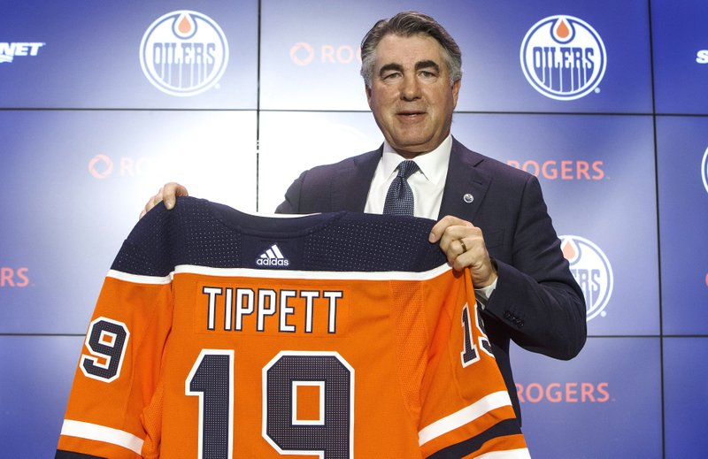 Edmonton Oilers new NHL hockey team head coach Dave Tippett holds up a jersey during a press conference in Edmonton, Alberta, Tuesday, May 28, 2019. (Jason Franson/The Canadian Press via AP)