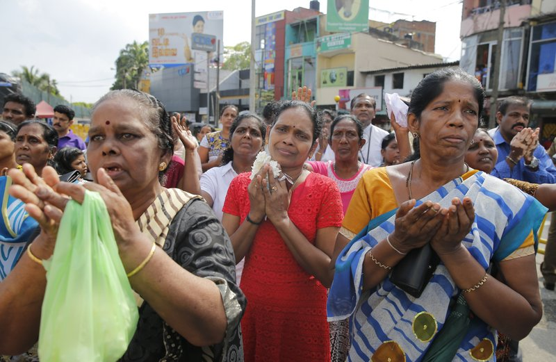 Sri Lankan Roman Catholic devotees pray out Side the St. Anthony's church, one of the sites of Easter Sunday attacks in Colombo, Sri Lanka, Tuesday, May 21, 2019. More than 250 people were killed in coordinated suicide bomb attacks at three churches and three tourist hotels on Easter Sunday that were claimed by the Islamic State group and carried out by a local radicalized Muslim group. (AP Photo/Eranga Jayawardena)