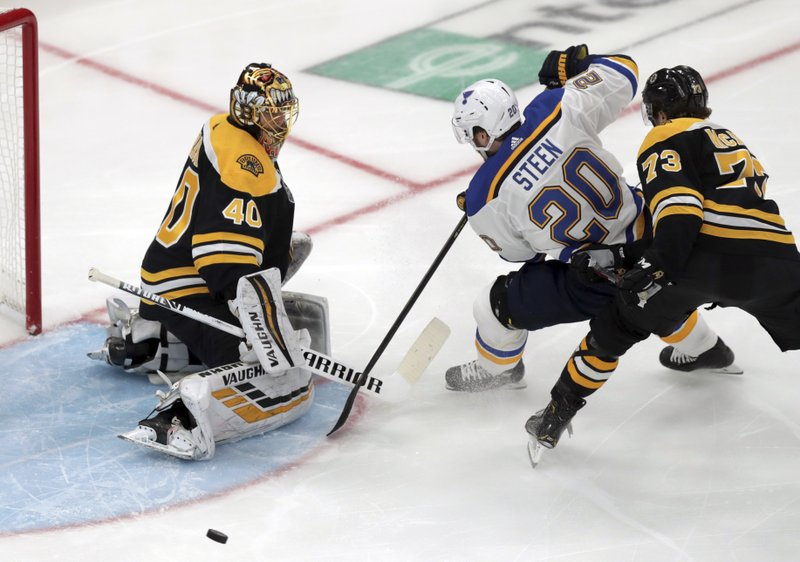 Boston Bruins goaltender Tuukka Rask (40), of Finland, turns the puck away as St. Louis Blues' Alexander Steen (20) tries to score during the third period in Game 1 of the NHL hockey Stanley Cup Final, Monday, May 27, 2019, in Boston. Bruins' Charlie McAvoy defends at right. (AP Photo/Charles Krupa)