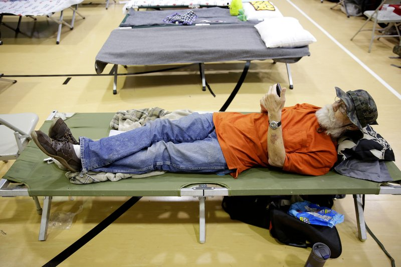 J.D. Morgan lies on a cot at the Red Cross evacuation shelter at Crosstown Church after leaving his home at 78th Street and Wheeling Ave. in south Tulsa due to the Arkansas River flooding Tuesday, May 28, 2019. (Mike Simons/Tulsa World via AP)
