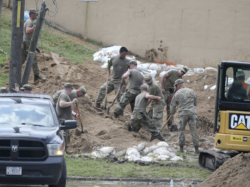 National Guardsman and Corps of Engineers workers fill sand bags behind a levee that was bubbling earlier Tuesday, May 28, 2019 in Tulsa, Okla. (Tom Gilbert/Tulsa World via AP)
