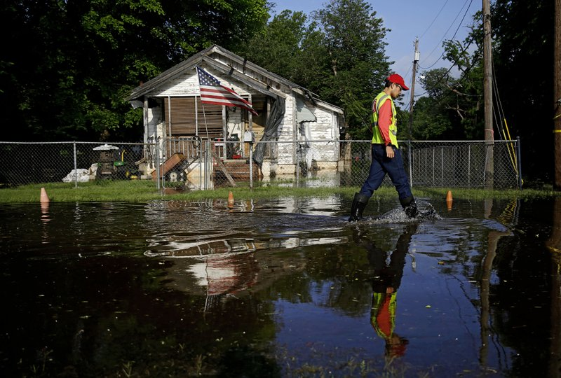 John Castro of the United States Army Corps of Engineers surveys flooding in a west Tulsa neighborhood on South 51st West Ave at West 12th Street Tuesday, May 28, 2019.. (Mike Simons/Tulsa World via AP)