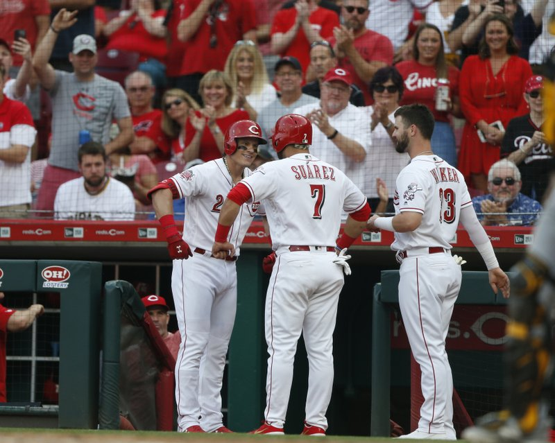 Cincinnati Reds' Derek Dietrich, left, celebrates a two-run home run off Pittsburgh Pirates starting pitcher Jordan Lyles with Eugenio Suarez (7) and Jesse Winker (33) during the fourth inning of a baseball game, Tuesday, May 28, 2019, in Cincinnati. (AP Photo/Gary Landers)