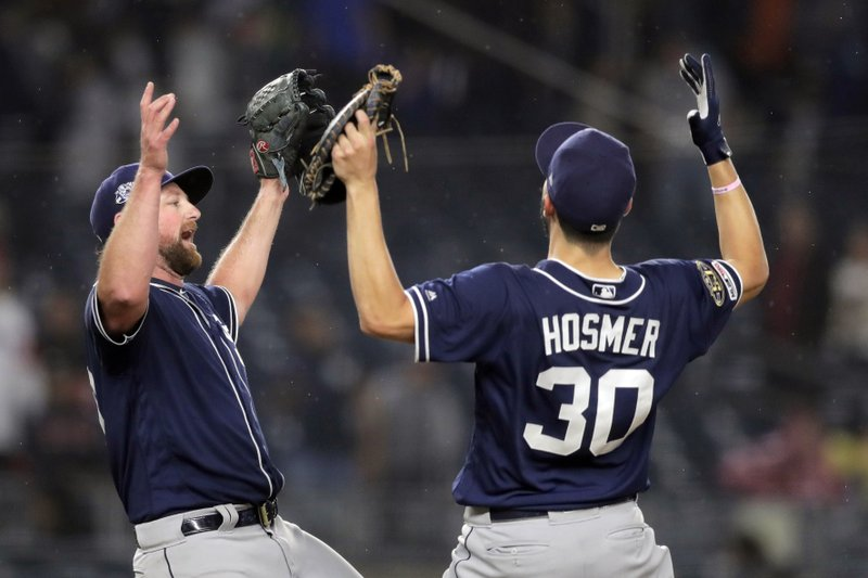 San Diego Padres relief pitcher Kirby Yates, left, and first baseman Eric Hosmer (30) react after defeating the New York Yankees 5-4 in a baseball game, Tuesday, May 28, 2019, in New York. (AP Photo/Julio Cortez)