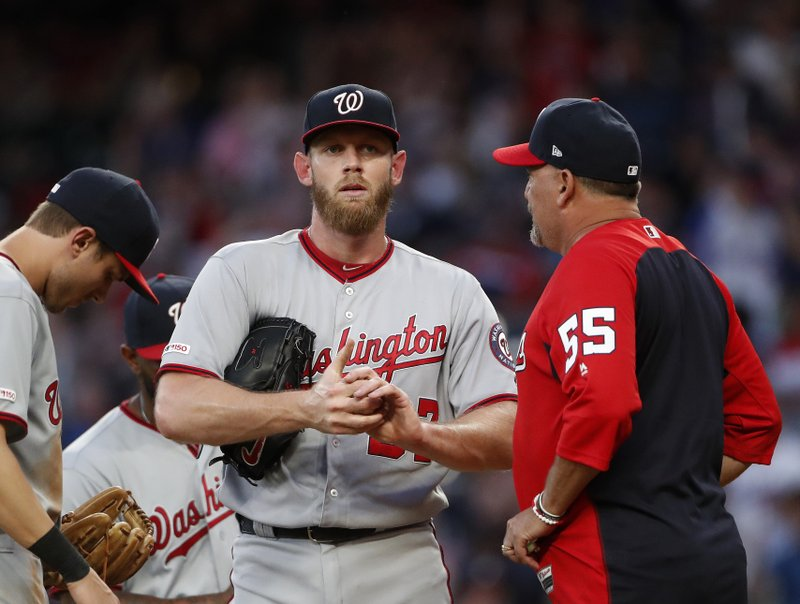 Washington Nationals starting pitcher Stephen Strasburg (37) talks with pitching coach Paul Menhart (55) during the fourth inning of a baseball game against the Atlanta Braves, Tuesday, May 28, 2019, in Atlanta. (AP Photo/John Bazemore)
