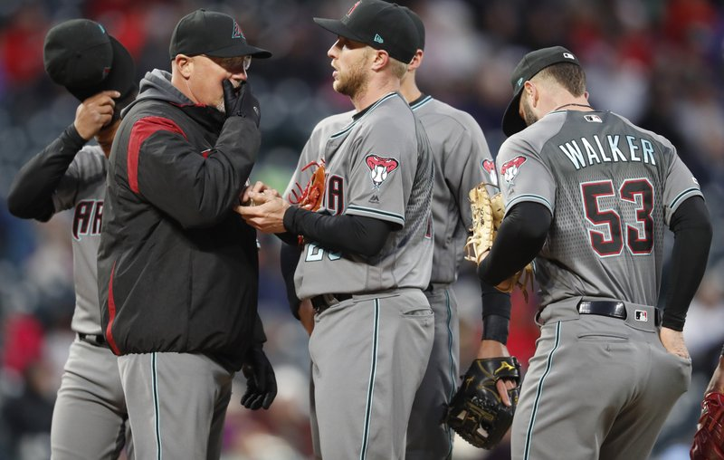 Arizona Diamondbacks pitching coach Mike Butcher, left, confers with starting pitcher Merrill Kelly as first baseman Christian Walker, right, looks on after Kelly gave up an RBI double to Colorado Rockies' Daniel Murphy in the fourth inning of a baseball game, Tuesday, May 28, 2019, in Denver. (AP Photo/David Zalubowski)