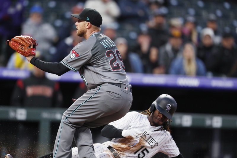 Arizona Diamondbacks starting pitcher Merrill Kelly, front, looks for the throw from catcher Alex Avila as Colorado Rockies' Raimel Tapia scores on a passed ball in the fourth inning of a baseball game Tuesday, May 28, 2019, in Denver. (AP Photo/David Zalubowski)