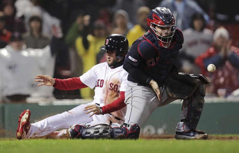 Cleveland Indians catcher Roberto Perez, right, tries to control the ball as Boston Red Sox's Michael Chavis, left, scores on a double by Steve Pearce in the eighth inning of a baseball game at Fenway Park in Boston, Tuesday, May 28, 2019. (AP Photo/Charles Krupa)