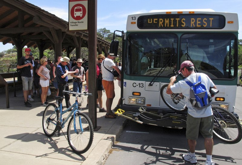 FILE - In this Aug. 19, 2015 file photo, a visitor loads his bike on a shuttle bus at Grand Canyon National Park in northern Arizona. A new report from the National Park Service says areas surrounding the Grand Canyon benefited last year from millions of tourism dollars. Grand Canyon National Park officials say the report found the 6.3 million people who visited in 2018 spent $947 million in communities near the park. (AP Photo/Felicia Fonseca, File)