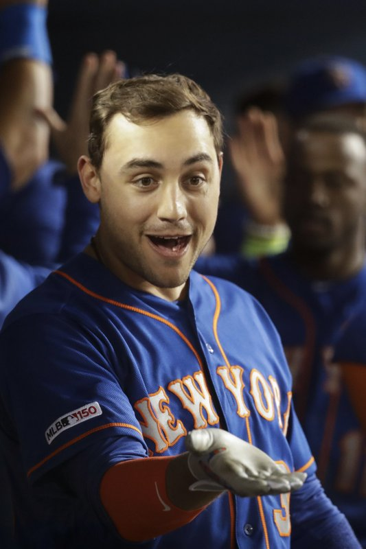 New York Mets' Michael Conforto celebrates in the dugout after his grand slam against the Los Angeles Dodgers during the seventh inning of a baseball game in Los Angeles, Tuesday, May 28, 2019. (AP Photo/Chris Carlson)