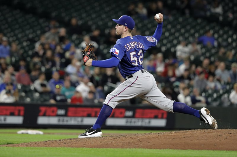 Texas Rangers starting pitcher Adrian Sampson throws during the sixth inning of a baseball game against the Seattle Mariners, Tuesday, May 28, 2019, in Seattle. Rangers pitcher Jesse Chavez pitched for the first inning. (AP Photo/Ted S. Warren)