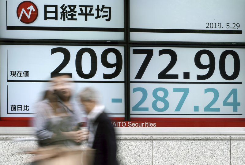 People walk past an electronic stock board showing Japan's Nikkei 225 index at a securities firm in Tokyo Wednesday, May 29, 2019. Asian shares slipped Wednesday on expectations that a trade dispute between China and the United States would simmer and possibly weigh on growth.(AP Photo/Eugene Hoshiko)