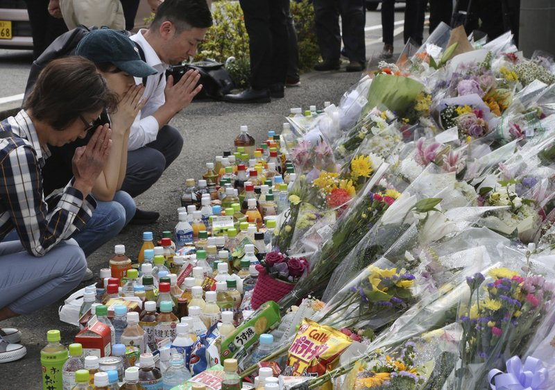 People pray for victims at the site where a knife attack took place in Kawasaki near Tokyo Wednesday, May 29, 2019. A man carrying a knife in each hand and screaming