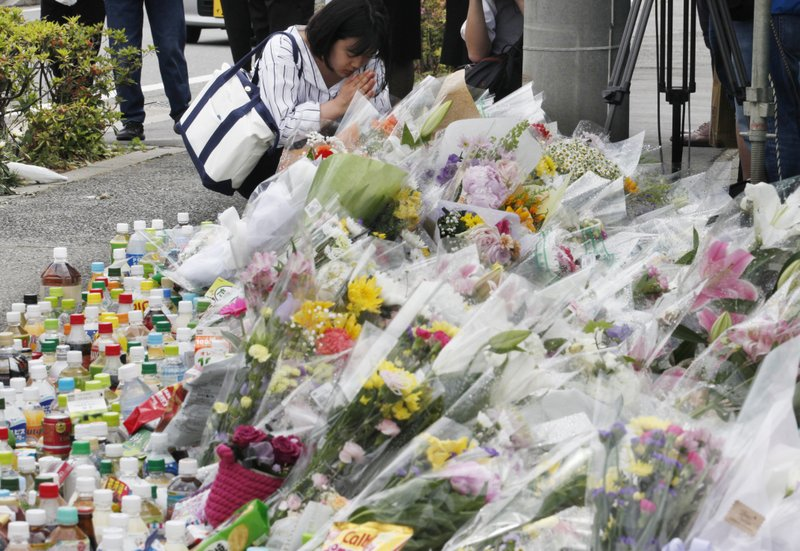 A woman prays for victims at the scene where a knife attack took place in Kawasaki near Tokyo Wednesday, May 29, 2019. A man carrying a knife in each hand and screaming