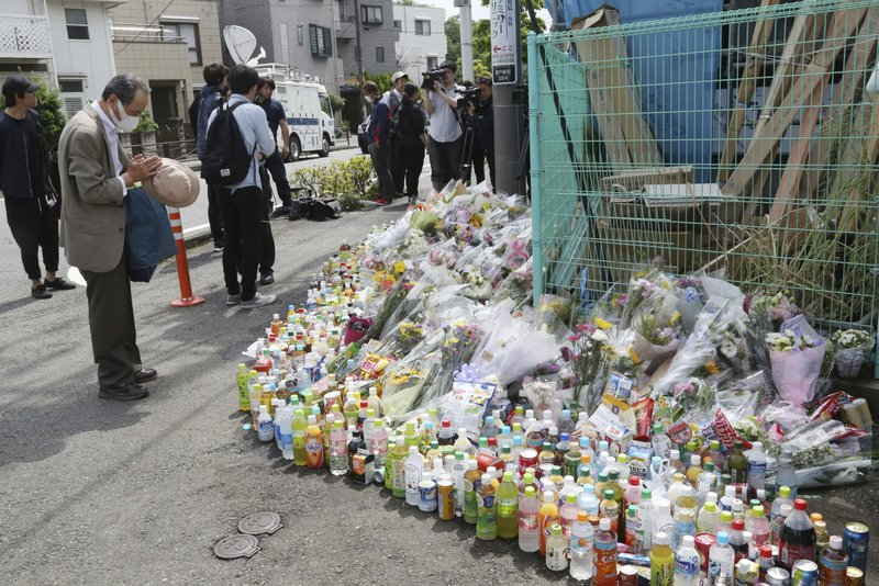 A man prays for victims at the site where a knife attack took place in Kawasaki near Tokyo Wednesday, May 29, 2019. A man carrying a knife in each hand attacked a group of schoolgirls waiting at a bus stop just outside Tokyo Tuesday. (AP Photo/Koji Sasahara)