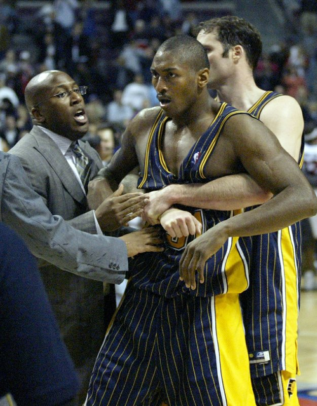 FILE - In this Nov. 19, 2004, file photo, Indiana Pacers' Ron Artest, now known as Metta World Peace, is restrained by teammate Austin Croshere and Pacers assistant coach Mike Brown before being escorted off the court following their fight with the Detroit Pistons and fans in Auburn Hills, Mich. Metta World Peace needed to win a championship ring so his career wasn't defined only by one angry moment in Detroit. (AP Photo/Duane Burleson, File)