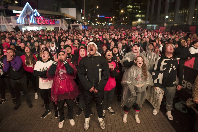FILE - In this Sunday, May 12, 2019, file photo, basketball fans cheer for the Toronto Raptors before claiming victory over the Philadelphia 76ers outside Maple Leaf Square during their NBA Eastern Conference semifinal basketball game in Toronto. For Raptors games, Maple Leaf Square, aka Jurassic Park, boasts a college vibe of rowdy fans crammed into an area that covers two city blocks. (Tijana Martin/The Canadian Press via AP, File)