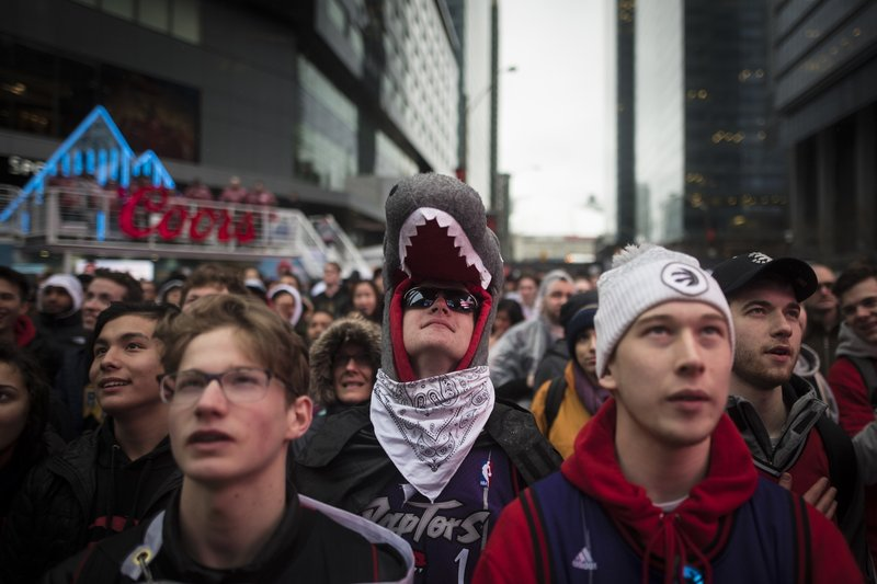 FILE - In this Sunday, May 12, 2019, file photo, Owen Smith, center, dresses up to show his support at the Jungle Park tailgate party at Maple Leaf Square in Toronto, as the Toronto Raptors prepare to play the Philadelphia 76ers during Game 7 of the NBA Eastern Conference semifinals. For Raptors games, Maple Leaf Square, aka Jurassic Park, boasts a college vibe of rowdy fans crammed into an area that covers two city blocks. (Tijana Martin/The Canadian Press via AP, File)