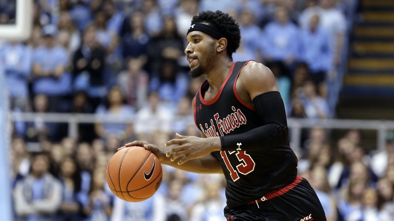 FILE - In this Monday, Nov. 19, 2018, file photo, St. Francis guard Keith Braxton (13) dribbles the ball during the second half of an NCAA college basketball game against North Carolina in Chapel Hill, N.C. The rule adopted by the NCAA amid the college basketball scandal and that is designed to help players explore their pro potential and still return to school surprisingly applies only to Division I players. Braxton, a 6-5 guard, signed with an agent but hopes he has generated NBA interest as he returns for his senior season after withdrawing from the draft. (AP Photo/Gerry Broome, File)