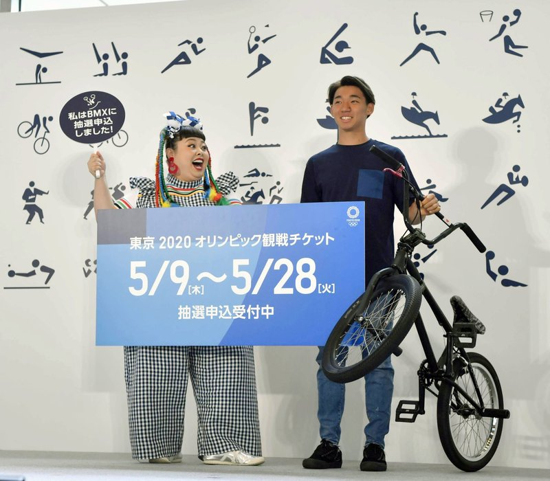 FILE - In this May 8, 2019, file photo, Japanese comedian Naomi Watanabe, left, and BMX rider Rimu Nakamura attend an event to mark the start of application to buy tickets for the 2020 Tokyo Olympic Games, in Tokyo. Tokyo Olympic organizers say millions of Japan residents have shown interest in buying tickets for next year's games. Organizers closed the first phase of ticket applications on Wednesday, May 29, 2019, for Japan residents, and applicants will be told on June 20 what tickets they have been allocated through a lottery system. The sign reads