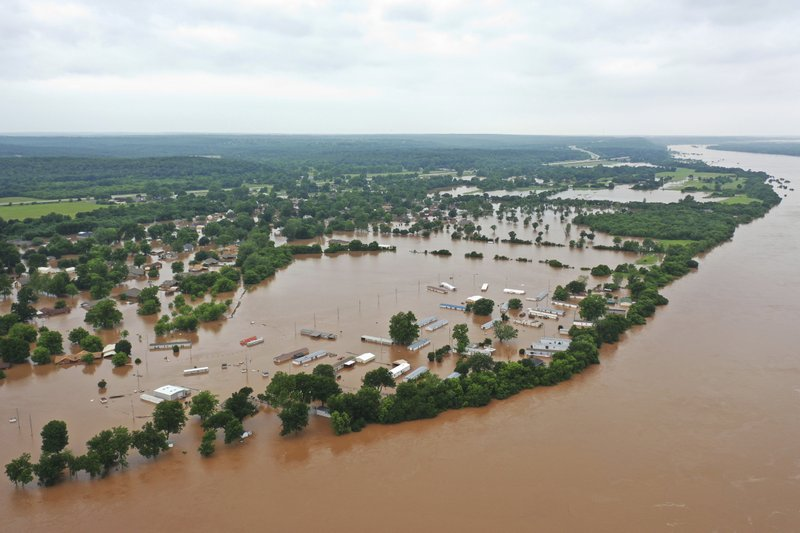 This May 28, 2019 aerial photo shows flooded homes along Arkansas River in Sand Spring, Okla. Communities that have seen little rain are getting hit by historic flooding along the Arkansas River thanks to downpours upstream that have prompted officials to open dams to protect some cities but inundate others with swells of water. (DroneBase via AP)