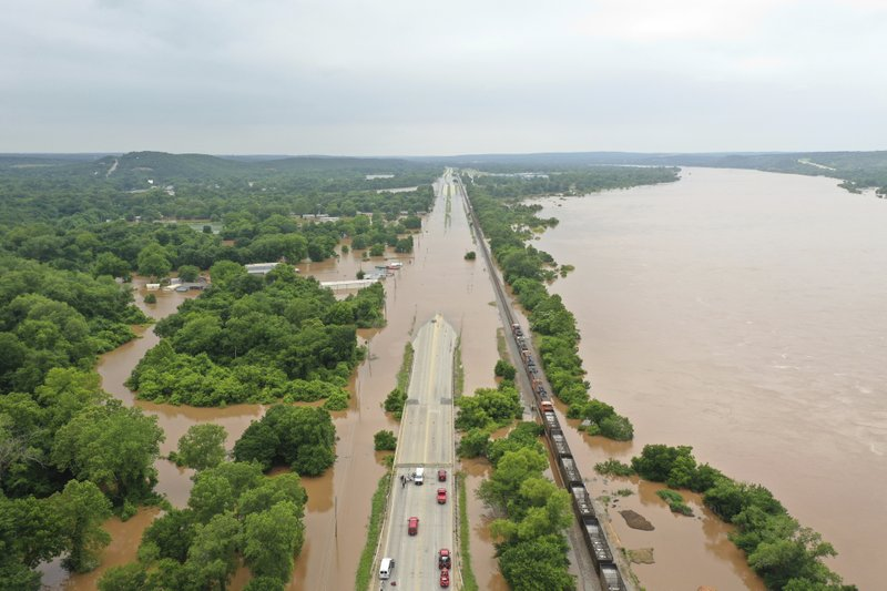 This Tuesday, May 28, 2019 aerial photo shows a flooded highway Arkansas River in Sand Spring, Okla. Communities that have seen little rain are getting hit by historic flooding along the Arkansas River thanks to downpours upstream that have prompted officials to open dams to protect some cities but inundate others with swells of water. (DroneBase via AP)