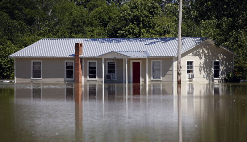 In this Thursday, May 23, 2019 photo, floodwaters overtake a home in Holly Bluff, Miss. It's month four of an epic flood in the Mississippi Delta, where some people are still struggling to save their homes and some farmers are realizing they won't plant a single acre this year. (AP Photo/Rogelio V. Solis)