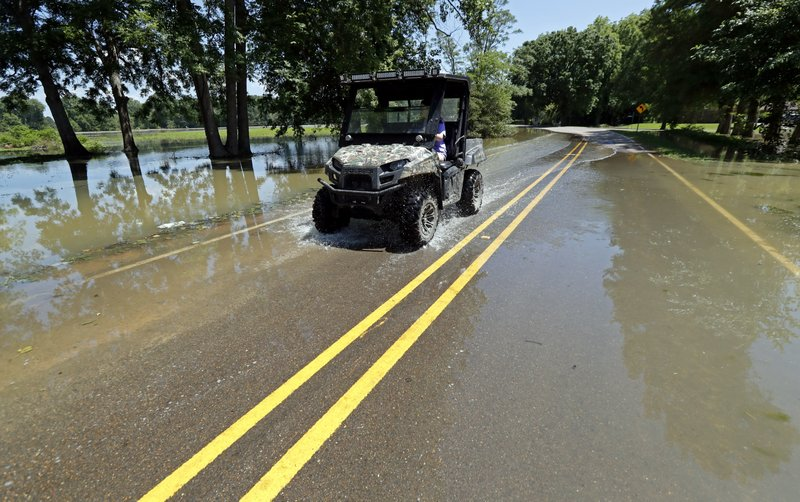 In this Thursday, May 23, 2019 photo, a Holly Bluff, Miss., resident drives through backwater flooded streets. It's month four of an epic flood in the Mississippi Delta, where some people are still struggling to save their homes and some farmers are realizing they won't plant a single acre this year. Floodwater now covers 860 square miles north of Vicksburg, and nobody knows for sure when it will be gone. (AP Photo/Rogelio V. Solis)