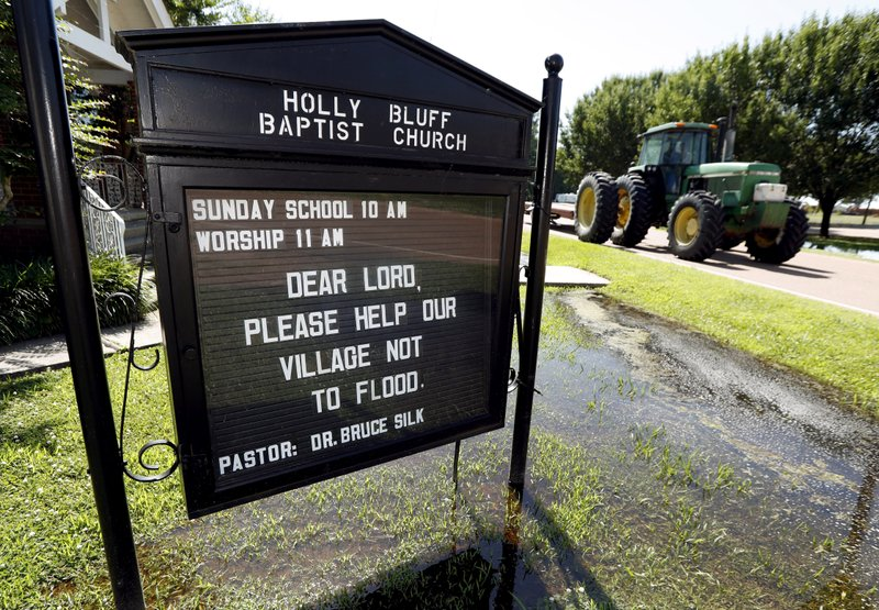 In this Thursday, May 23, 2019 photo, a tractor rolls past a posted prayer sign at the Holly Bluff Baptist Church calling for the small Mississippi Delta farming community to be spared from the backwater flooding that has overtaken 860 square miles north of Vicksburg since mid-February. Members ringed the small church with sandbags as waters began to creep onto its property. (AP Photo/Rogelio V. Solis)