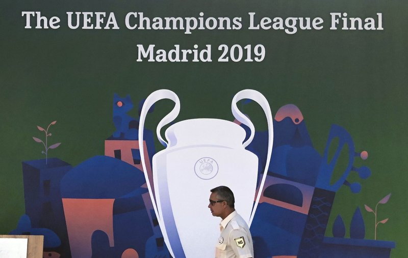 An employee from a security firm walks past a Champions League banner in downtown Madrid, Spain, Wednesday, May 29, 2019. Madrid will be hosting the final again after nearly a decade, but the country's streak of having at least one team playing for the European title ended this year after five straight seasons, giving home fans little to cheer for when Tottenham faces Liverpool at the Wanda Metropolitano Stadium on Saturday. (AP Photo/Tales Azzoni)
