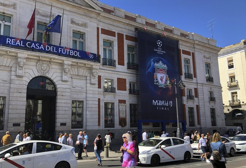 Pedestrians walk past Champions League banner in downtown Madrid, Spain, Wednesday, May 29, 2019. Madrid will be hosting the final again after nearly a decade, but the country's streak of having at least one team playing for the European title ended this year after five straight seasons, giving home fans little to cheer for when Tottenham faces Liverpool at the Wanda Metropolitano Stadium on Saturday. (AP Photo/Tales Azzoni)