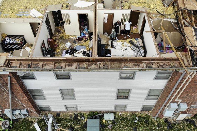 Residents sort through apartments open up to the air Tuesday, May 28, 2019, at the Westbrooke Village Apartments in Trotwood, Ohio, after the roof was torn off from a severe storm the night before. (AP Photo/John Minchillo)