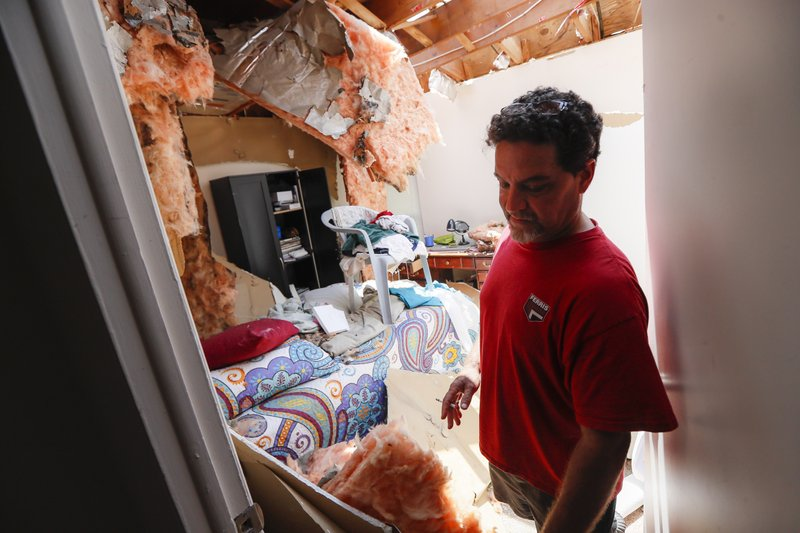 Shaun Vaine walks through his destroyed home at the River's Edge apartment complex, Tuesday, May 28, 2019, in Dayton, Ohio, the day after a tornado struck the city. (AP Photo/John Minchillo)