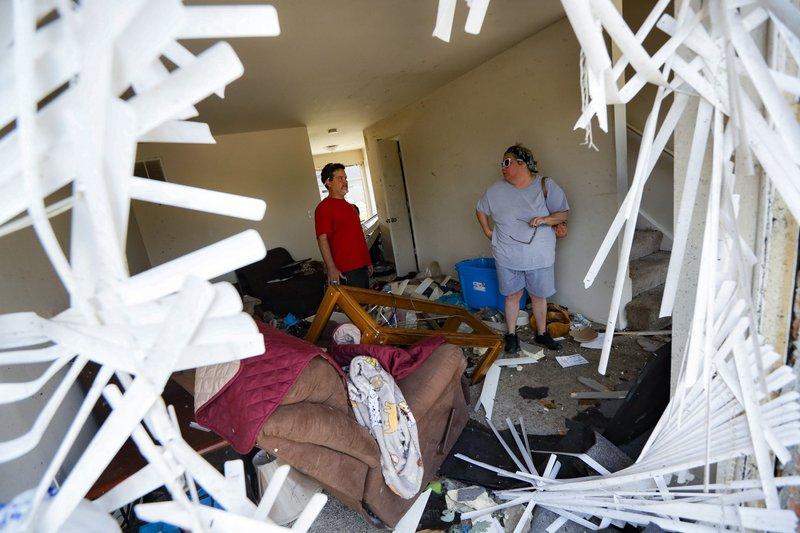 Shaun Vaine, left, and Michele Thrash, right, stand in their destroyed home at the River's Edge apartment complex, Tuesday, May 28, 2019, in Dayton, Ohio, the day after a tornado struck the city. (AP Photo/John Minchillo)