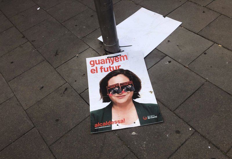 An electoral poster with a portrait of Barcelona's mayor Ada Colau is seen on the ground in Barcelona, Catalonia, Spain, Monday, May 27, 2019. Three jailed or fugitive Catalan politicians want to turn their freshly won seats in the European Parliament as a loudspeaker for their separatist cause in northeastern Spain - although being actually sworn in as lawmakers will be the first obstacle to overcome. (AP Photo/Emilio Morenatti)
