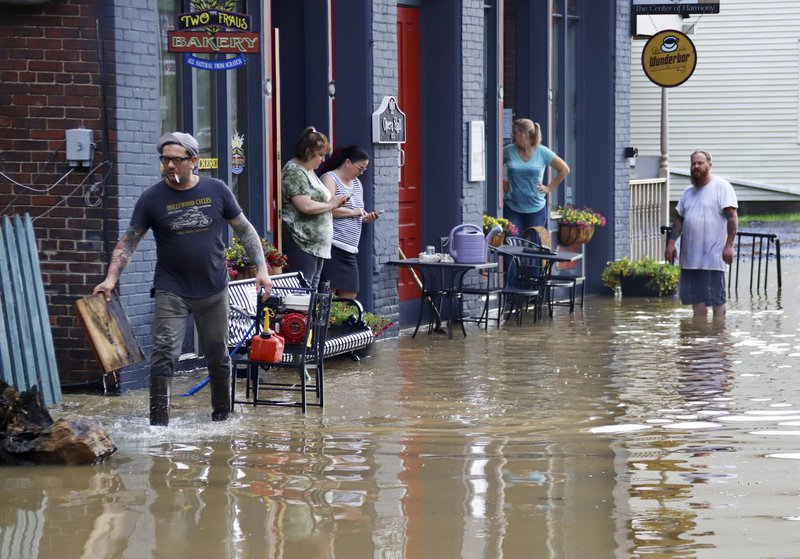 Business owners and workers assess flood damage as they to start cleanup, Wednesday, May 29, 2019, in Harmony, Pa. More storms are predicted for the area. (AP Photo/Keith Srakocic)