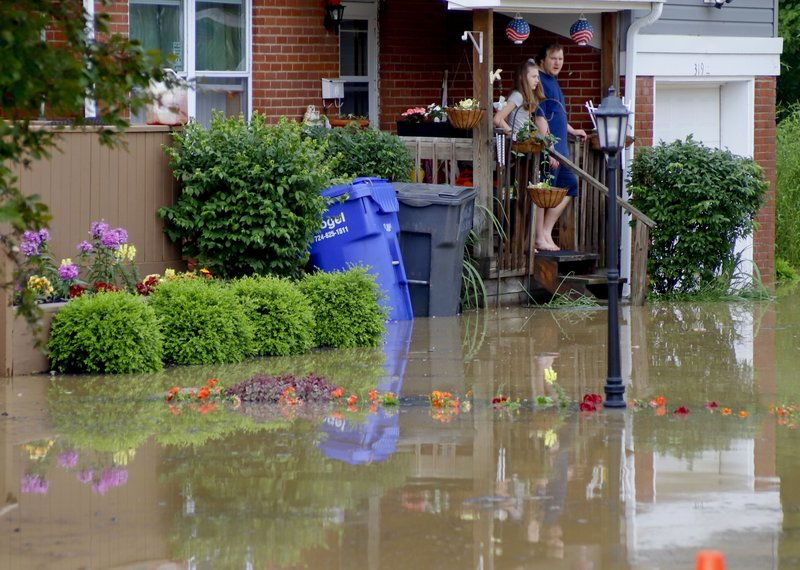 People stand on the porch of a house that is surrounded by floodwaters, Wednesday, May 29, 2019, in Zelienople, Pa. More storms are predicted for the area. The Mayor of Zelienople, Thomas Oliverio, declared a State of Emergency Tuesday night after heavy rain caused the flooding. (AP Photo/Keith Srakocic)