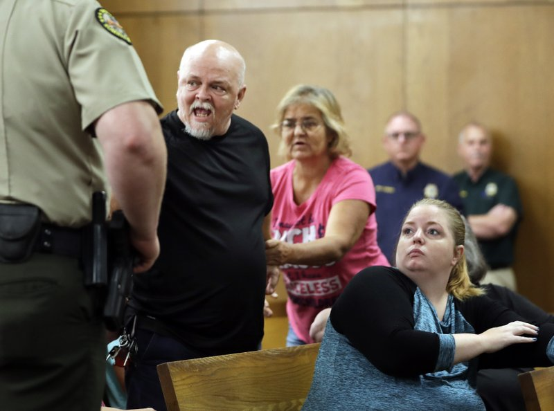 Steve McGlothlin is escorted out of the courtroom after he yelled out as he heard testimony in the preliminary hearing for Michael Cummins Wednesday, May 29, 2019, in Gallatin, Tenn. Cummins faces multiple counts of first-degree murder in connection with the deaths of eight people in a nearby rural community in April. McGlothlin is a relative of some of the victims. (AP Photo/Mark Humphrey)